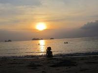 Mädchen am Strand während dem Sonnenuntergang